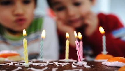 Two children looking at candles on a birthday cake