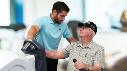 An older man in a black hat sitting at a machine while a McLeod Rehabilitation Specialist explains what he needs to do