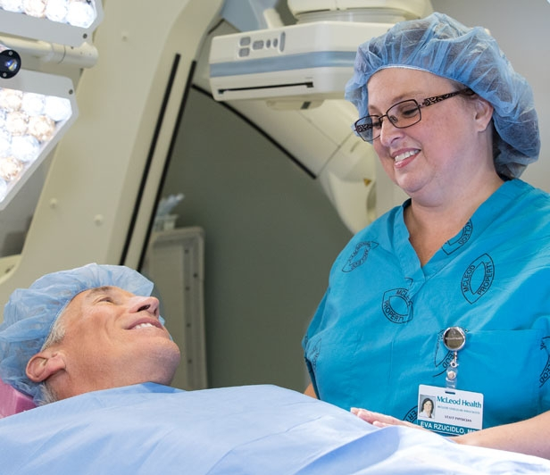 A man smiling at a nurse during preparations for a vascular surgical procedure