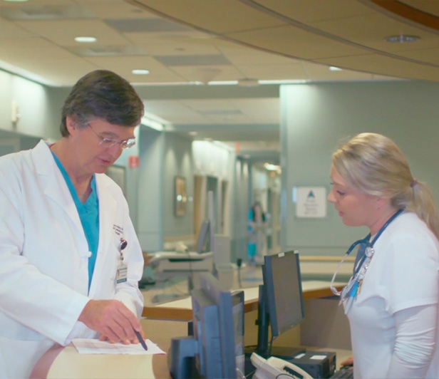 Dr. Wayne Holley, a Thoracic Surgeon, speaking with a nurse at a medical office desk