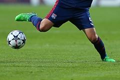 A soccer player wearing a blue uniform winding up to kick a soccer ball