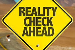 A yellow road sign reading: REALITY CHECK AHEAD