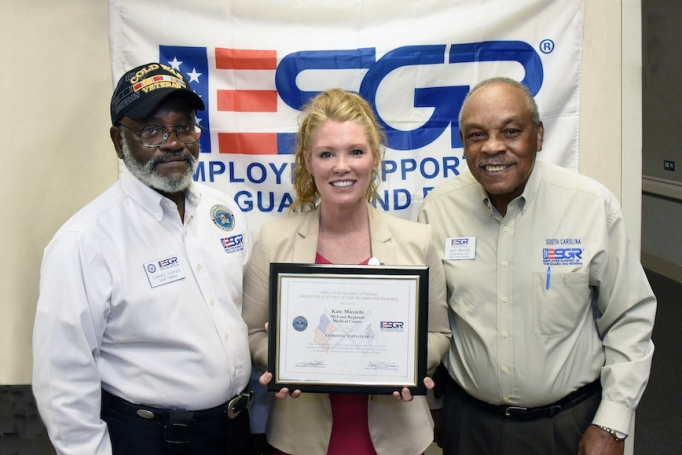 Kate Miccichi, McLeod's Director of Patient Relations, holding an award given to her by the Employer Support of the Guard and Reserve organization