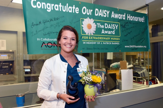 Beth Gleason, a staff nurse in the Trauma Surgical Care Unit, posing with McLeod Heath's DAISY Award