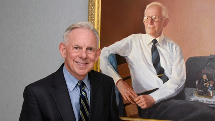 Dr. Charles Jordan, who was instrumental in creating McLeod Children's Hospital, standing next to a portrait of himself