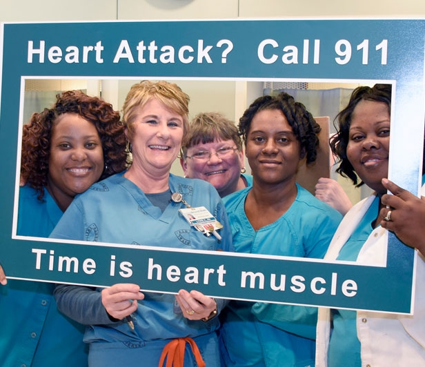 McLeod Health cardiatric nurses holding a sign encouraging people to call 911 at the first sign of a heart attack