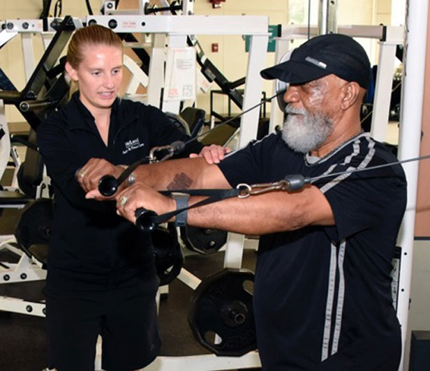 An older man using a chest press exercise machine at the McLeod Health & Fitness Center while a McLeod Health trainer supervises