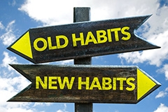 A sign pointing to old habits and sign pointing the opposite direction towards new habits