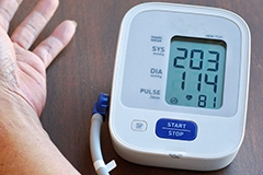 A person's hand next to a blood pressure monitor showing a reading of 203 over 114