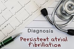 An EKG, stethoscope and a doctor's diagnosis note reading: persistent arterial fibrillation