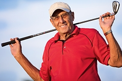 An older man wearing a golfing polo and carrying a golf club over his shoulder
