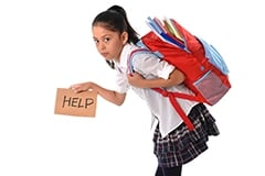 A young girl in a school uniform hunched over, carrying a backpack and holding a sign that says help