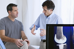 A doctor explaining knee replacement surgery to a man while an x-ray is also visible in the foreground