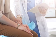 A doctor holding a female patient's hand while reviewing a medical file with her