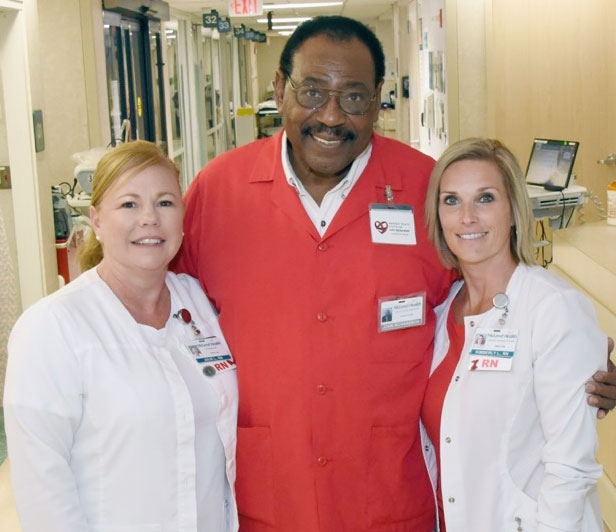 Two smiling McLeod nurses standing with a doctor in a red lab coat