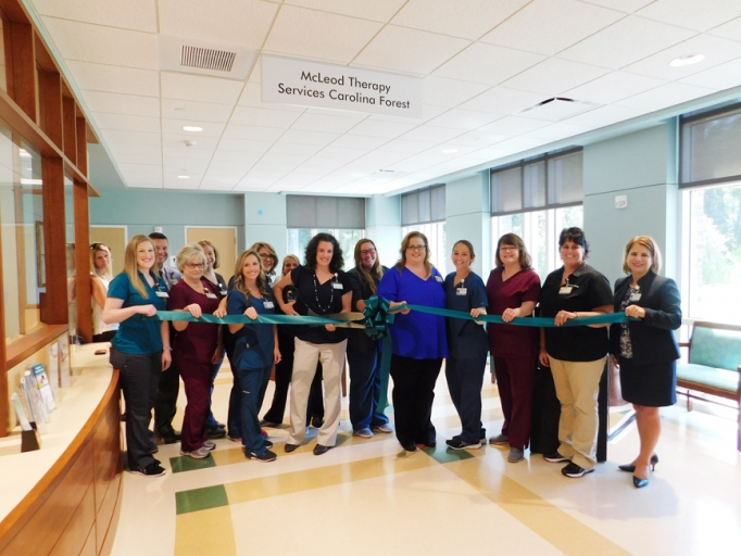 Staff and administrators cutting the ribbon for the McLeod Pediatric Rehabilitation office in Carolina Forest