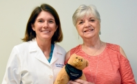 Linda Brown and Dr. Amy Murrell posing with a small teddy bear called a Breast Bear which helps comfort breast cancer patients