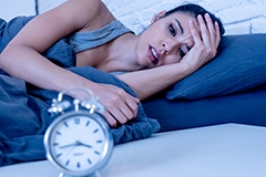 A woman in distress staring at a clock while in bed