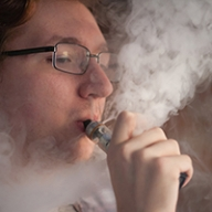 A young man with glasses using a vaping device