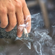 A lit cigarette billowing smoke while being held between a person's fingers