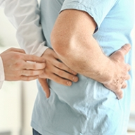 A doctor touching the lower back of a patient