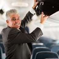 A man in a suit putting his bag in an overhead bin on an airplane