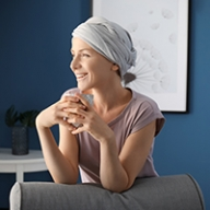 A female cancer patient smiling while wearing a head wrap