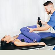 A woman's legs being stretched by a male doctor