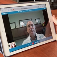 A doctor talking with a patient via a tablet device