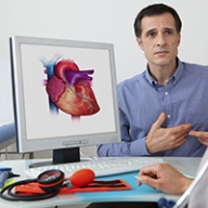A patient talking to a doctor while a heart diagram is on a computer screen