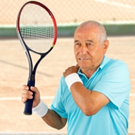 An older man grabbing his shoulder with discomfort while playing tennis