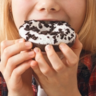A young child eating a sugary donut