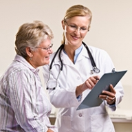 A female doctor showing a clipboard while talking to an older female patient