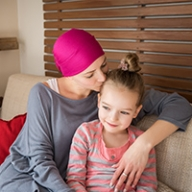 A woman cancer patient hugging a young girl