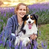 A woman holding a collie-like dog
