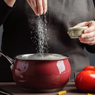 A cook sprinkling a good deal of salt into a cooking pot