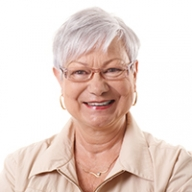 A smiling older woman with white hair