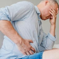 A man holding the side of his stomach in pain