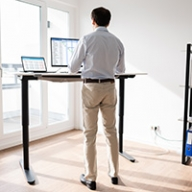 A man using a standing desk in a bright room